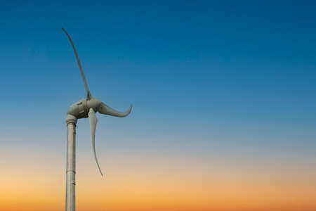 small wind turbine in sunset sky, clean energy for people
