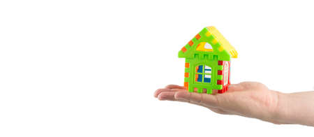 woman hand holding small toy house, house purchase concept, space for text