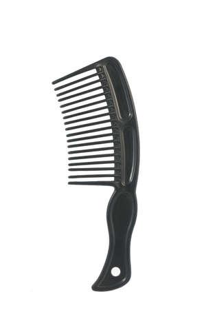 Black plastic comb on white background, close up image