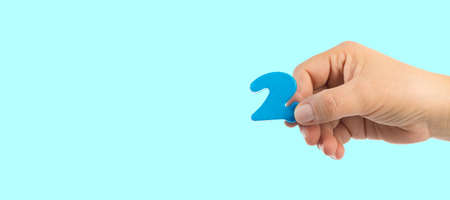 Woman's hand holding plastic number 2 symbol, close up image Stock fotó