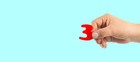 Woman's hand holding plastic number 3 symbol, close up image