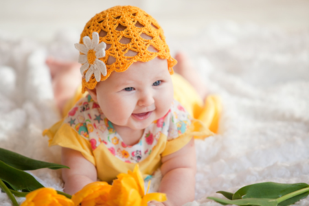 baby girl in a yellow dress and a crocheted yellow hat lying on the bed with yellow tulips