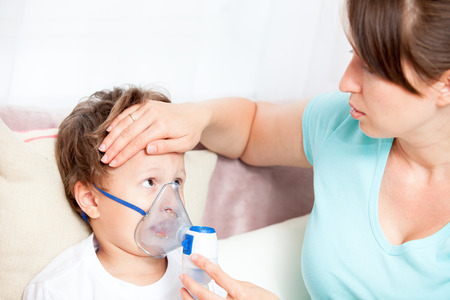 inhalation: Young woman doing inhalation with a nebulizer son and touches his forehead