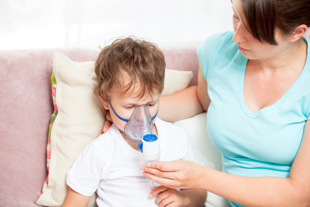 Young woman with son doing inhalation with a nebulizer at home Foto de archivo