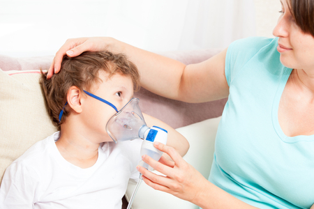 Young woman with son doing inhalation with a nebulizer at home Stock Photo