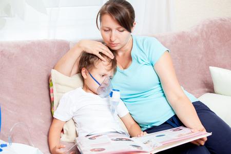 집에서 nebulizer와 흡입을하고 책을 읽는 아들과 젊은 여자 스톡 콘텐츠