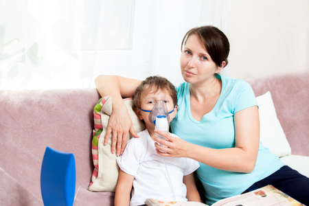 Young woman with son doing inhalation with a nebulizer at home and read a book