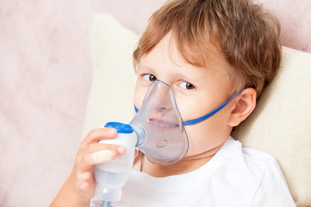 Boy making inhalation with a nebulizer at home Stock Photo