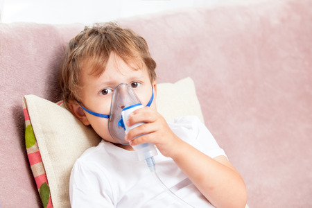 inhalation: Boy making inhalation with a nebulizer at home Stock Photo