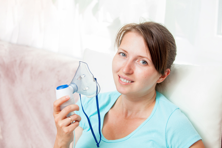 inhalation: Young woman doing inhalation with a nebulizer at home