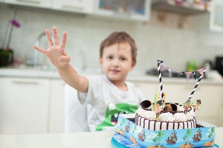 그 소년은 테이블에있는 케이크와 함께 앉아서 그가 얼마나 오래 있었는지 보여줍니다.