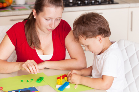A young woman with a son having fun playing in clay Stock Photo