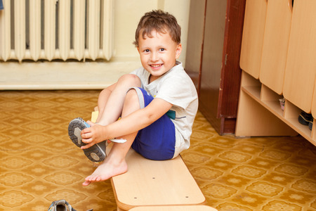 The child puts on shoes in kindergarten