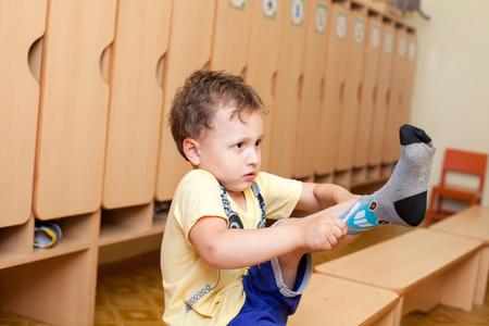 El niño lleva los calcetines en el jardín de infantes Foto de archivo - 64183637