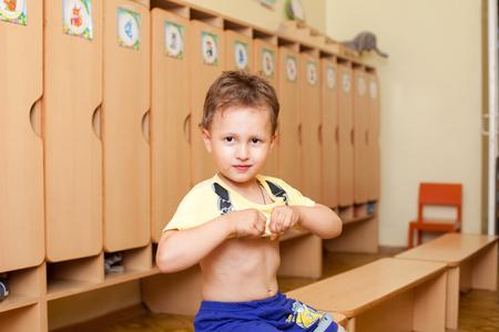 niños vistiendose: El niño lleva una camiseta en el jardín de infantes Foto de archivo