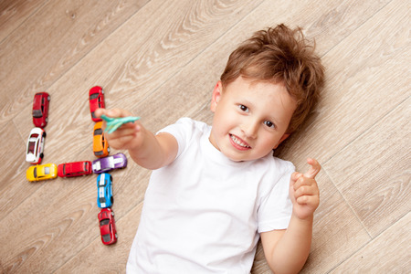 juguetes de madera: happy boy playing on floor with toy cars