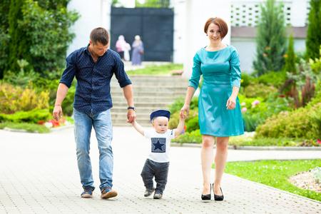 Pappa en mamma zijn over het handvat van zijn jonge zoon in het park