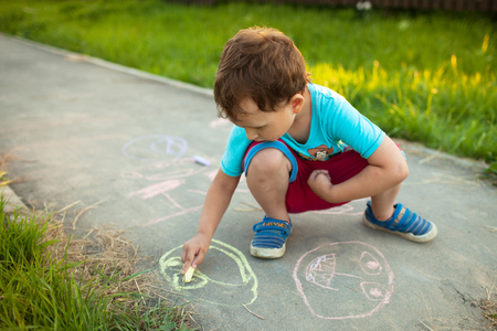 Boy draws with chalk on the pavement around the house Stock Photo