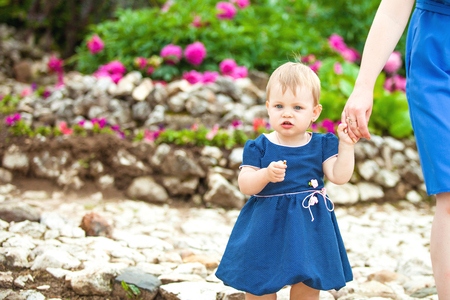 flowerbeds: A girl in a blue polka-dot dress walks in the Park with flowerbeds Stock Photo