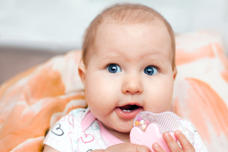 surprised baby: The surprised baby bodysuit with hearts and rattle Stock Photo