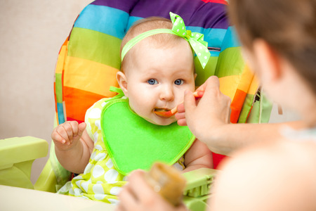 smudgy: the child eats a vegetable puree on the highchair