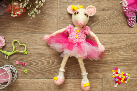 Knitted amigurumi mouse was lying on the floor, and around her button, candle holder with candle, a bouquet of roses