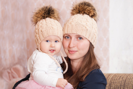 devotee: A young woman with her daughter in the same knitted caps