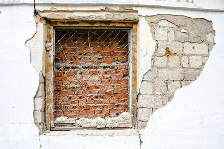 lattice window: window with rusty bars on the old wall with bricks Stock Photo