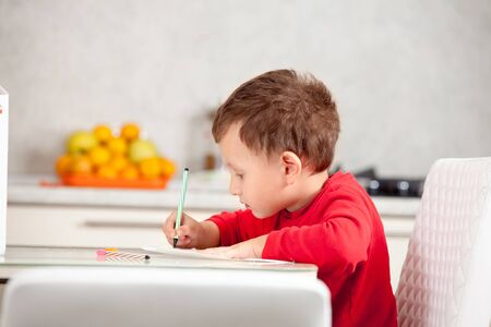 inspired: Inspired by the boy draws a picture on the paper at the table