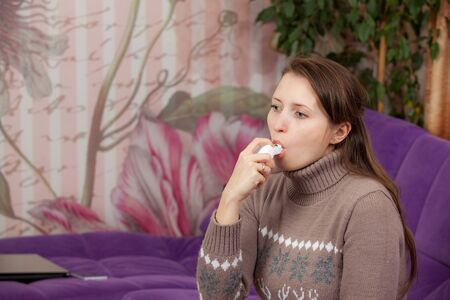 Woman uses an inhaler during an asthma attack