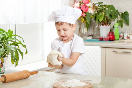 baby knead the dough in flour