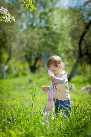 Little girl walking in the garden with a toy hare tilde Banco de Imagens