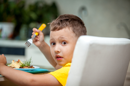 Happy little boy eating a healthy dinner at the table Stock Photo