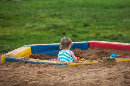 모래 상자에서 혼자 그리고 모두에서 멀리 재생하는 어린 소녀. 자폐성. 의사 소통의 문제.