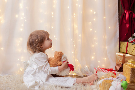 girl sitting looking at Christmas tree