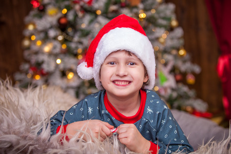 baby boy in Santa hat looking wide smiling. the room is decorated with Christmas lights all in lights. elegant snow-covered Christmas tree in the focus. family holiday Christmas pleases the child