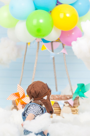 a small child looks at a bundle of colored balloons filled with helium tied to a wooden pilot basket. located in the sky among the clouds. heaven's decoration. Stock Photo