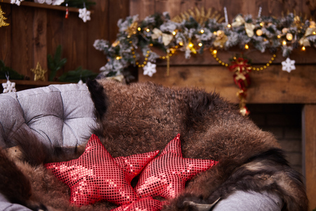 The comfort of Christmas in front of the fireplace arm chair with leather in dark colors. fur skin lying on a rattan chair. red pillows with shiny elements are sewn in the shape of a star 免版税图像