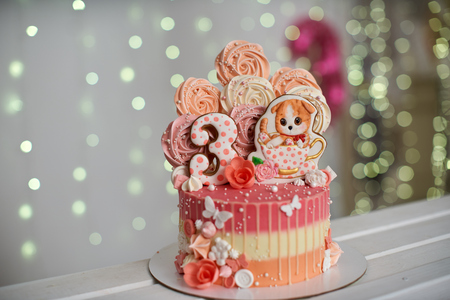 birthday cake for 3 years decorated with butterflies gingerbread kitten with icing and the number three. meringue pale pink in the shape of a rose or flower. meringue is a lot of cake decoration