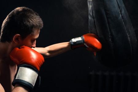 Boy hitting the punching bag on dark background