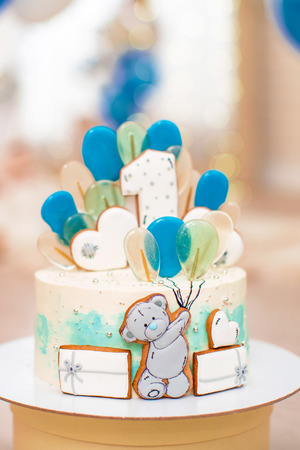 birthday cake for 1 year decorated with balloons gingerbread bear with icing. Stock Photo
