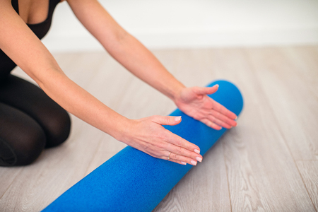 Beautiful woman in sportswear, Pilates instructor stretching and warming up with foam roller, with free text space.