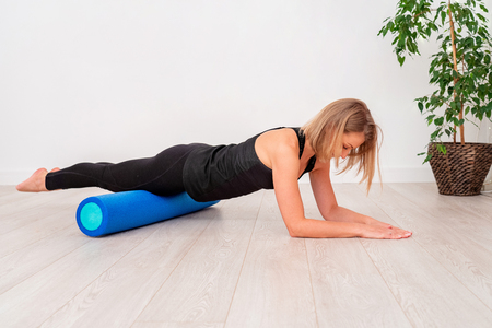 Beautiful woman in sportswear, Pilates instructor stretching and warming up with foam roller. The plank exercise with emphasis on the roll fitness. with free text space. Foto de archivo - 118977218