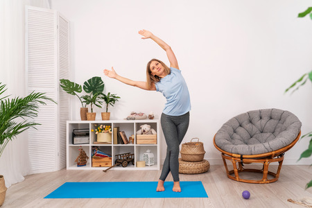 beautiful young blonde woman, stretching the muscles of her arms and back, performs gymnastic exercises at home. with free text space