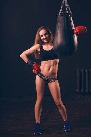 the boxer woman closed her fists in a gesture of readiness for battle. the confident strut of a boxer female. in the arms of a punching bag