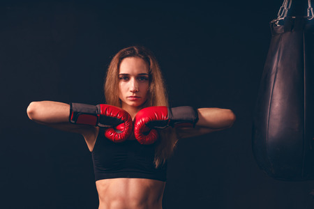 the boxer woman closed her fists in a gesture of readiness for battle. the confident strut of a boxer women
