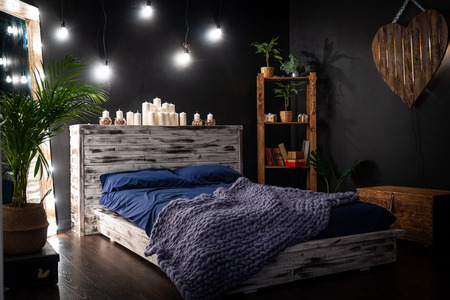 the bedroom is a dark room, with a mirror framed by light bulbs