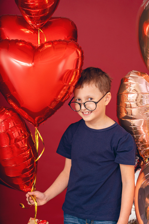 funny kid boy in glasses, different color heart, star balloons for valentines day or birthday on red background with free text space Banco de Imagens