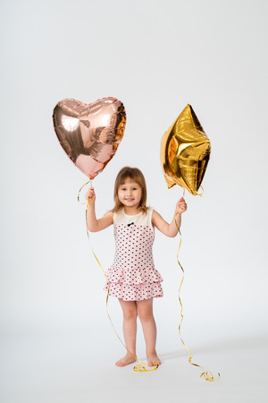 baby with heart shaped balloons and stars on white background Archivio Fotografico