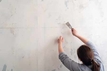 woman tears off Wallpaper, removing Wallpaper from the wall with a spatula, the process of updating the wall room repair. with free text space Imagens